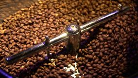 Slow motion shooting of coffee beans that are mix during frying, top view
