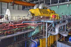 Machine room in thermal power plant with generators and turbines. Machine room in thermal power plant with electric generators and turbines Royalty Free Stock Photo
