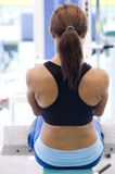 Machine Row. A female fitness instructor works out on a back row machine Stock Photos