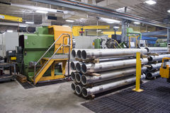 Machine shop interior. With manufactured steel tubes in foreground Stock Image