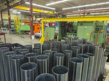 Machine shop interior. Machine shop floor with milled tubes in foreground Stock Images