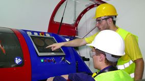 Two machine technicians set the machine. The machine technician performs computer control of the working machine stock footage