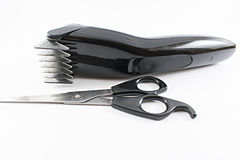 Machine to cut the hair and a scissors. stock images