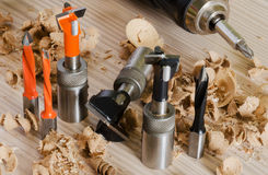 Machine tool cutters and drill bits. In the sawdust on wood background Royalty Free Stock Image