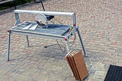 A machine-tool with a steel saw stands outside on a sidewalk Stock Photos