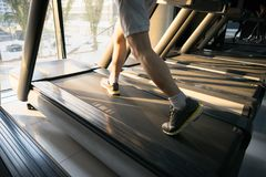 Machine treadmill with people running closeup at fitness gym Stock Images