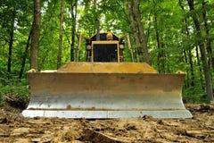 Machine versus Nature. Bulldozer standing in forest for deforestation Stock Photos