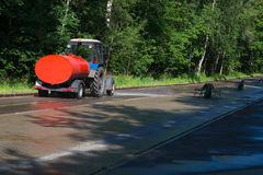 The machine washes and cools the road in the park. Big machine with water pouring path in the park Stock Photography