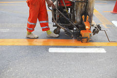 Machine and worker at road construction Stock Photo
