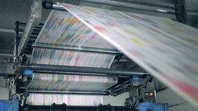 A machine works, rolling printed newspaper in typography facility. 4K stock video footage