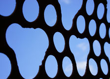 Machined holes in sieve with sky background Royalty Free Stock Photos