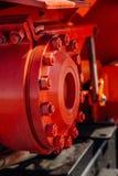 Machinedeel Verbinding van flenzen door bouten en gekleurd noten rood De mening van de close-up stock afbeeldingen