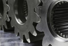 Machineparts concept. Close-up of three cogs, gears on stainless-steel royalty free stock image