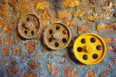 Machinery Cogs. Rusty cogs on a stone wall royalty free stock photo