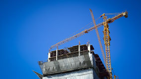 Machinery crane working in construction site building. Industry with blue sky background Royalty Free Stock Image