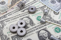 Machinery parts and US Dollar banknotes. Gearwheels and bolts on top of US Dollar (USD) banknotes Stock Photo