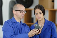 Machinery repairman worker ans female apprentice. Mechanic royalty free stock images