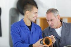 Machinery repairman worker processing metal piece in workshop Stock Photos