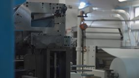Machinery shop. Die cutting of paper blanks for disposable tableware production. Machinery shop. Punching machine. Die cutting of paper or carton templates for stock video footage