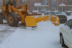 Machinery with snowplough cleaning road by removing snow from intercity after winter snow storm Stock Images
