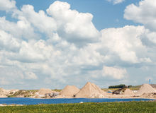 Machinery working in the distance at gravel pit under  vast big sky. Large gravel pit with machinery and equipment in the distance sitting next to a lake and a Stock Image