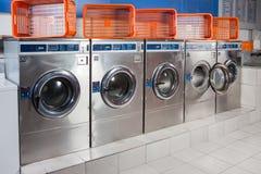 Machines à laver et paniers vides dans une rangée images stock