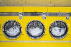 Machines à laver jaunes de pièce de monnaie avec la blanchisserie dans elle photographie stock