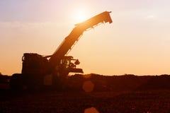 Machines agricoles dans le coucher du soleil Photos stock