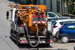 Machines de décapant d'eaux d'égout près des voitures se garantes images stock