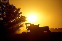 Machines for harvesting in from the sun. Machines for harvesting in from the evening sun Stock Photos