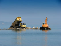 Machines in sea. Excavator and lorry working in the sea Stock Photos