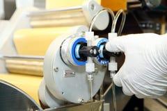 Machinevervaardiging van gelatinecapsules Bevestiging van de machineman Productie van capsules voor tabletten Royalty-vrije Stock Foto's