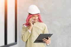 Machinez le téléphone portable utilisé par homme arabe et tenez le document pour le travail photos stock