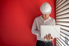 Machinez le travail avec l'ordinateur portable dans l'espace rouge de bâtiment Photos libres de droits