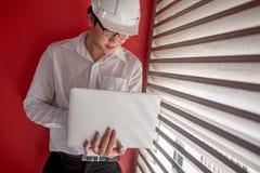 Machinez le travail avec l'ordinateur portable dans l'espace rouge de bâtiment Images libres de droits