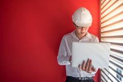 Machinez le travail avec l'ordinateur portable dans l'espace rouge de bâtiment Image libre de droits