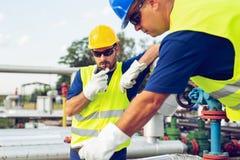 Machinez le travail dans un raffinerie de pétrole avec parler sur la radio portative pour le travail de contrôle images stock