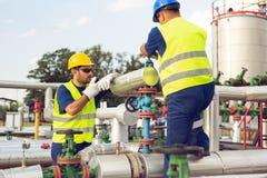 Machinez le travail dans un raffinerie de pétrole avec parler sur la radio portative pour le travail de contrôle image stock