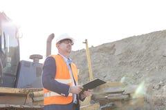 Machinez regarder parti tout en tenant le presse-papiers le chantier de construction Photographie stock libre de droits