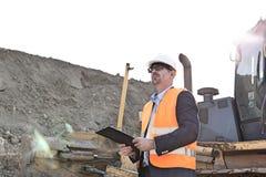 Machinez regarder parti tout en tenant le presse-papiers le chantier de construction Images libres de droits