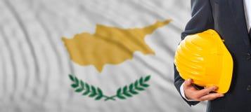 Machinez tenir un casque antichoc jaune sur le fond de ondulation de drapeau de la Chypre illustration 3D Images stock