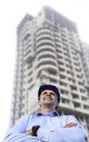 Machinez travailler à un chantier portant un casque de protection se tenant sur le fond de bâtiment photo libre de droits