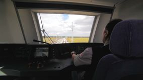 Machinist drives train in cabin among yellow fields. Backside view skilled middle-aged machinist drives modern electric train in cabin among yellow fields stock footage