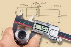 Hand and digital measuring tool. Machinist gauges the diameter of metal workpiece by the caliper and checks it with technical documentation Royalty Free Stock Photo