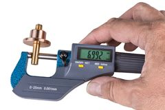 Human hand holding a digital micrometer close-up. Machinist when measuring a bronze and brass metallic part by the precise gauging device with a green display royalty free stock image
