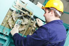 Machinist with spanner adjusting lift mechanism Stock Image