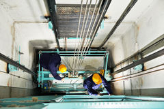 Machinist with spanner adjusting lift mechanism. Two male technician machinist worker at work adjusting elevator mechanism of lift with spanner Royalty Free Stock Images