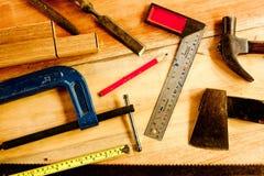Machinist vierkant, houten potlood, hamer, zaag, klem, Beitel, bankschroef, meetlint, dossier voor timmerman op houten achtergron royalty-vrije stock foto's