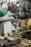 Machinist working on industrial drilling machine in workshop Stock Image