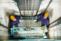 Machinists adjusting lift in elevator hoist way Royalty Free Stock Photo
